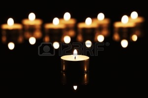 15220569-one-burning-tea-candle-in-front-of-many-burning-tea-candles-on-a-black-mirror